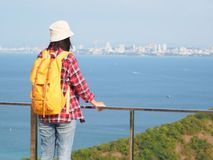 Travel , Women wearing Blue jeans and red plaid shirt and backpacking yellow at viewpoint on mountain are looking at the sea.  royalty free stock photo