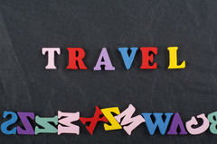 TRAVEL word on black board background composed from colorful abc alphabet block wooden letters, copy space for ad text Royalty Free Stock Image