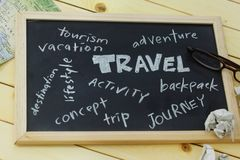Travel words cloud written on black board with maps,spectacles and crumpled paper. Stock Images