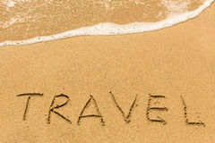 Travel - written manually on the texture of sea sand Stock Image