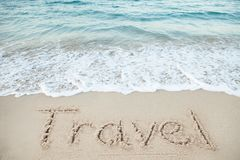 Travel Written On Sand By Sea Stock Photo
