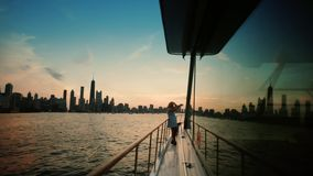 Travel on the yacht. Woman taking photo on smartphone of beautiful night city. wide shot.  stock video footage