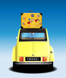 Travel - yellow retro car with travel suitcase on blue background Stock Photo