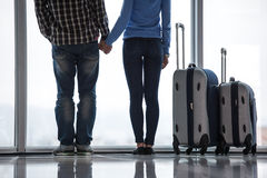 Travel. Young couple with suitcases are looking through airport window while waiting for flight. Back view Stock Photo