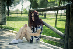 Travel, Young girl with straw hat sitting on a wooden bridge in Stock Photography