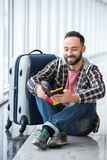 Travel. Young smiling man with a suitcase and passport ready to travel royalty free stock image