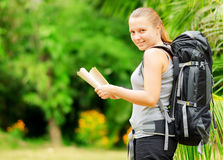 Young woman with backpack in a woods Stock Images