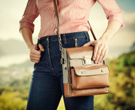Young woman in deep blue jeans holding a bag Royalty Free Stock Images