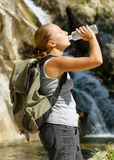 Young woman drinks water by waterfall Stock Image