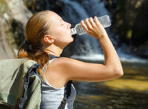 Young woman drinks water by waterfall Stock Photos