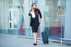 Travel. Young woman goes at airport at window with suitcase waiting for plane.  stock image