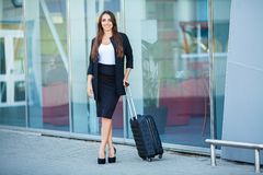Travel. Young woman goes at airport at window with suitcase waiting for plane.  royalty free stock photography