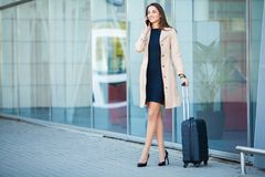 Travel. Young woman goes at airport at window with suitcase waiting for plane.  stock images