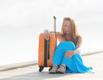 Young woman sitting on wooden pier.  Royalty Free Stock Image