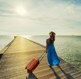 Young woman with suitcase waking on wooden pier Royalty Free Stock Images