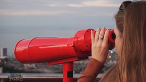 Travel: young woman tourist looking at city. Through coin-operated binoculars at sunset. Close-up shot, handheld, slow motion 60fps, HD stock footage