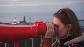 Travel: young woman tourist looking at city. Through coin-operated binoculars at sunset. Close-up shot, handheld, slow motion 60fps, HD stock video