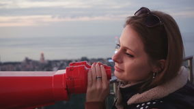 Travel: young woman tourist looking at city. Through coin-operated binoculars at sunset. Close-up shot, handheld, slow motion 60fps, HD stock video footage