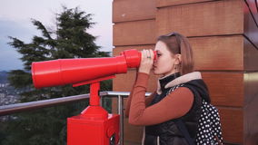 Travel: young woman tourist looking at city. Through coin-operated binoculars at sunset. Medium shot, handheld, slow motion 60fps, HD stock footage