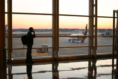Traveler. Male traveler at sunrise at Ronald Reagan airport, talking on cellphone stock photos
