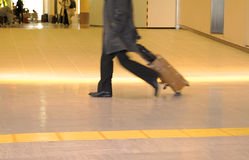 Traveler abstract. Motion blur image of a traveler carrying suitcase in an airport Royalty Free Stock Image