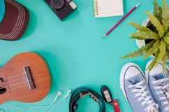Traveler accessories. Shoes, , ukulele, pencils and notebooks  and phone on the green background Stock Photos