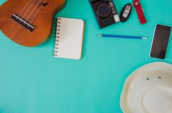 Traveler accessories. Hat, ukulele, pencils and notebooks. and phone on the green background Stock Image