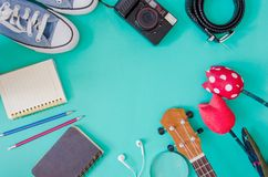 Traveler accessories. Shoes, , ukulele, pencils and notebooks  and phone on the green background Royalty Free Stock Images