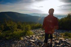 Traveler admiring sunset in mountains Stock Photos