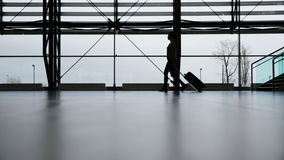 Traveler in airport terminal. Woman walking in airport terminal with her roller bag stock video footage