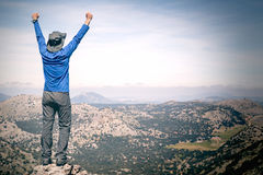 Traveler with arms up on mountain. Happy traveler with arms up looking at beautiful landscape against of blue sky while standing on top of mountain stock images