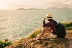 Traveler asia woman sitting on sea cliff Stock Photo