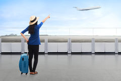 Traveler asian woman carrying suitcase looking airplane Royalty Free Stock Photography