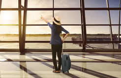 Traveler asian woman with suitcase looking sunset through window Stock Images