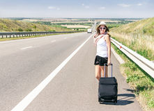Traveler attractive smiling girl is walking on highway. Royalty Free Stock Photo