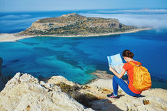 Traveler with backpack. Female traveler with backpack and map sitting on the cliff against sea and blue sky at early morning Stock Image
