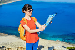 Traveler with backpack. Female traveler with backpack and map standing on the cliff against sea and blue sky at early morning Royalty Free Stock Photos