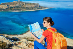 Traveler with backpack. Female traveler with backpack and map standing on the cliff against sea and blue sky at early morning Stock Images