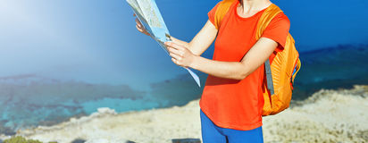 Traveler with backpack. Female traveler with backpack and map standing on the trail against sea and blue sky at early morning Stock Image