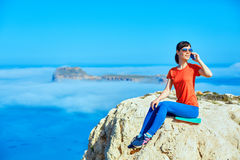 Traveler with backpack. Female traveler with backpack and phone sitting on the cliff against sea and blue sky at early morning. Balos beach on background, Crete Royalty Free Stock Images