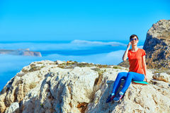 Traveler with backpack. Female traveler with backpack and phone sitting on the cliff against sea and blue sky at early morning. Balos beach on background, Crete Stock Images