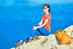 Traveler with backpack. Female traveler with backpack sitting on the cliff against sea and blue sky at early morning Royalty Free Stock Image