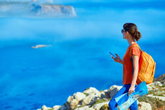 Traveler with backpack. Female traveler with backpack standing on the cliff against sea and blue sky at early morning. Balos beach on background, Crete, Greece Stock Image