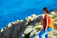 Traveler with backpack. Female traveler with backpack  standing on the trail against sea and blue sky at early morning Royalty Free Stock Photos