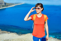 Traveler with backpack. Female traveler with backpack  standing on the trail against sea and blue sky at early morning Royalty Free Stock Image