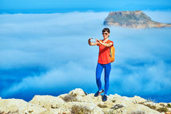 Traveler with backpack. Female traveler with backpack  standing on the trail against sea and blue sky at early morning. Balos beach on background, Crete, Greece Royalty Free Stock Photography
