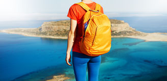 Traveler with backpack. Female traveler with backpack standing on the trail against sea and blue sky at early morning. Balos beach on background, Crete, Greece Stock Photos