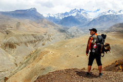 A traveler with a backpack in the Himalayan mountains looks at the gorge. Nepal. Kingdom of Upper Mustang. Stock Photo