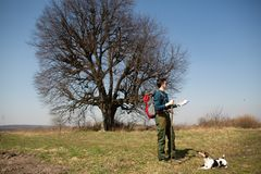 A traveler with a backpack and his dog, looking at the map and walking in the countryside royalty free stock image