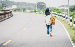 Traveler with backpack holding map and get lost,asian woman back. Packer standing on road and looking forward to see way,freedom journey concept,hitchhiker stock photo